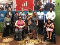 ODEP staff pose with colleagues in front of a sign at a USBLN public event.